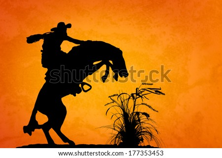 Silhouette of cowboy reigning bucking bronco spooked by something in the nearby sagebrush. Sunset orange/yellow textured background.