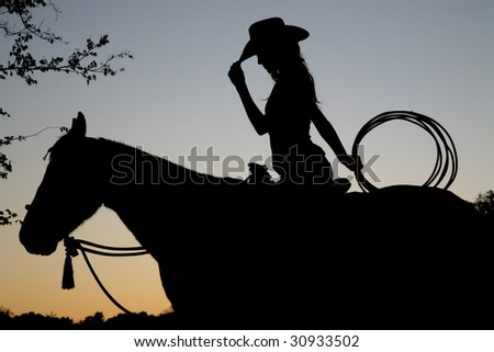 Silhouette of Cowgirl and Horse - stock photo