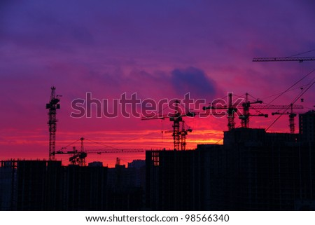 Silhouette of cranes on sunset sky background - stock photo