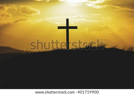 silhouette of cross and mountain with sunlight through cloudy sky background