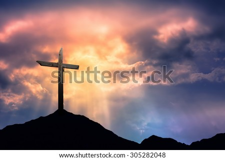 Silhouette of cross at sunrise or sunset with light rays - stock photo