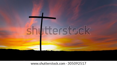 Silhouette of cross over red sunrise or sunset