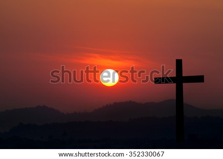 Silhouette of cross over sunset background