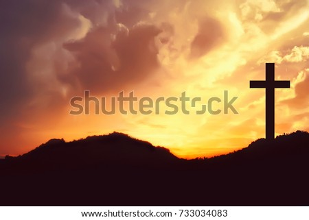 Silhouette of crosses symbol on the mountain peak with dramatic cloud on the sky at sunrise