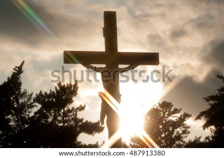 Silhouette of crucifix with dramatic lighting against cloudy sky