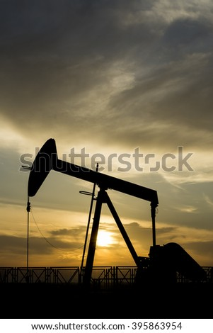 Silhouette of crude oil pump and cloudy sunset in the oil field.