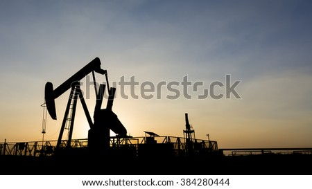 Silhouette of crude oil pump at sunset in oilfield.