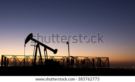 Silhouette of crude oil pump in oil field