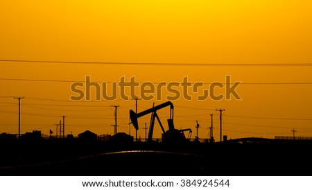 Silhouette of crude oil pump in oil field at sunset. - stock photo