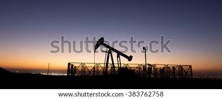 Silhouette of crude oil pump in oil field - wide view panorama