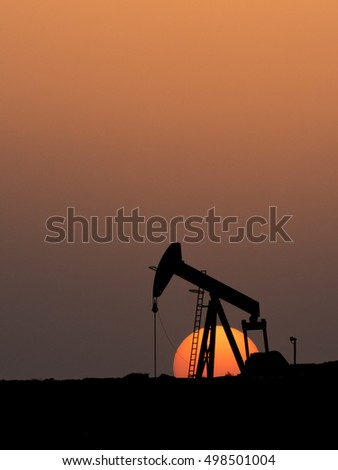 Silhouette of crude oil pumping unit at sunset in oil field