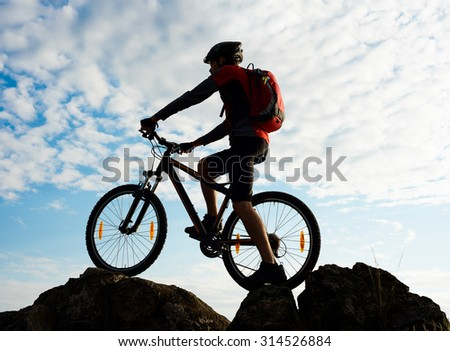 Silhouette of Cyclist with Bike on the Rock at Sunset. Extreme Sports Concept.