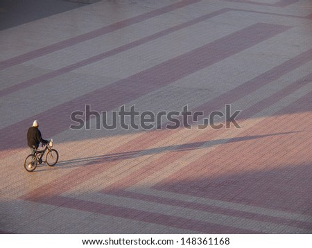 Silhouette of cyclists at sunrise, casting long shadows - stock photo