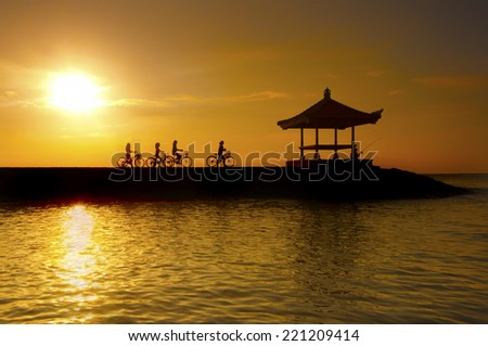 Silhouette of cyclists through wave barrier of Karang beach or Sanur beach in bali indonesia island one of the fabulous place to visit when you in Bali. - stock photo
