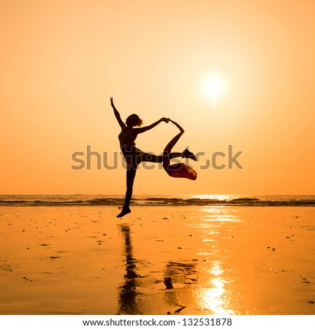 silhouette of dancing woman on the beach, inspiration - stock photo
