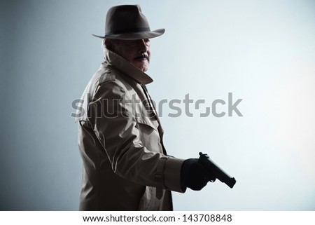 Silhouette of detective with mustache and hat. Holding gun. Studio shot. - stock photo