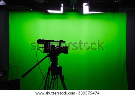 Silhouette of digital video camera in front of the green screen - stock photo