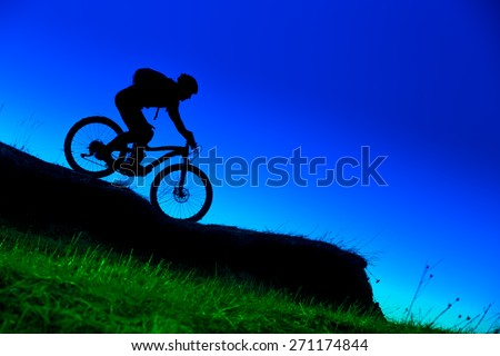 silhouette of downhill mountain bike ride at blue sky  - stock photo