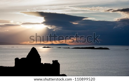Silhouette of Dunluce castle in Northern Ireland, county Antrim, against a clouded sky at sunset showing the spectral highlights and sunbeams hitting the Atlantic ocean - stock photo