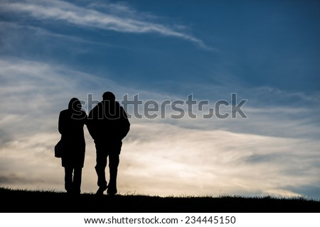 silhouette of elderly couple walking on hill  - stock photo