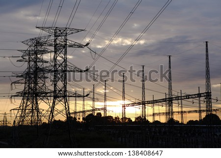 Silhouette of electricity power pylon line at a rural power distribution grid against a fiery sunset.