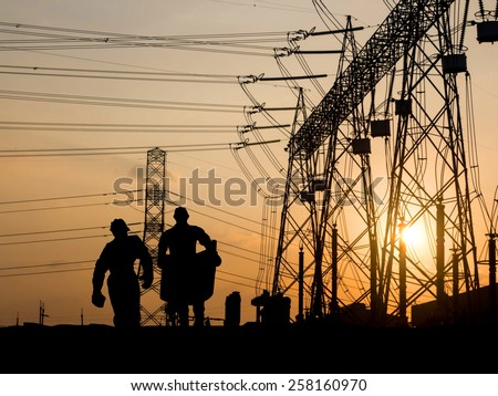 Silhouette of engineer looking at blueprints in a building site over Blurred substation - stock photo