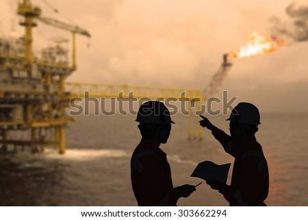 Silhouette of engineers looking at rig in sepia tone