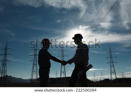 silhouette of engineers standing at electricity station shaking hands - stock photo