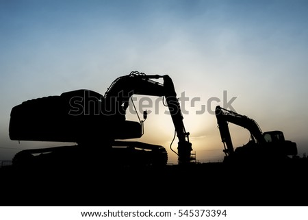 Silhouette of excavator at construction site in oilfield - sunset blue hour