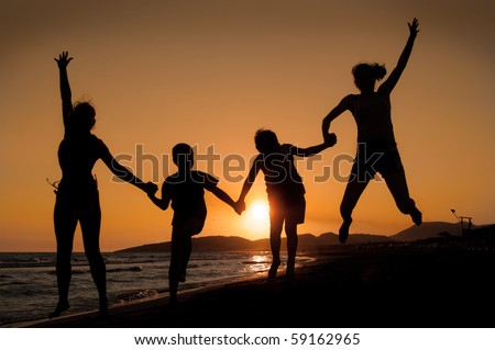 Silhouette of family jumping on the beach   on beautiful summer sunset