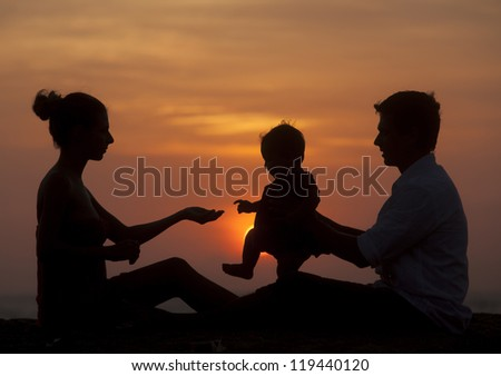 Silhouette of family sitting together at evening - stock photo