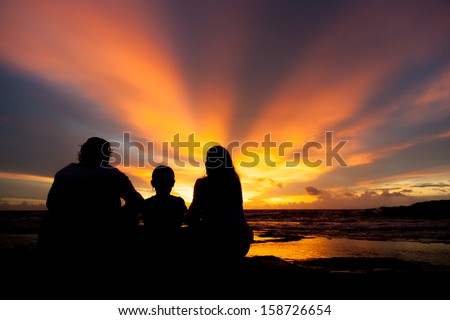 silhouette of family watching sunset at the beach in Phi Phi island - stock photo