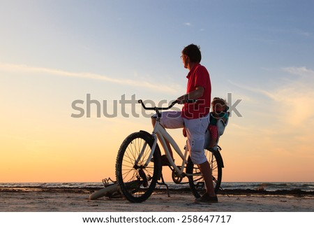 Silhouette of father and baby biking at sunset