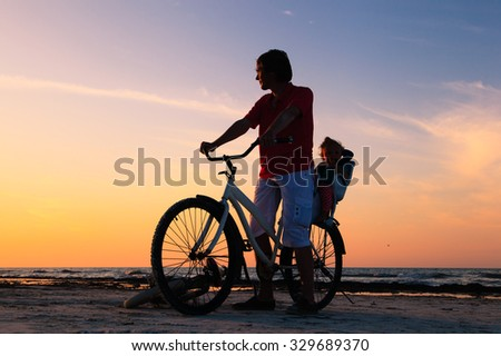 Silhouette of father and baby biking at sunset beach