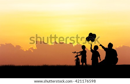 Silhouette of father and boy standing  sunset background