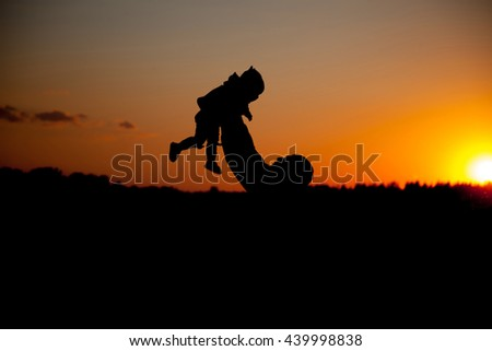 Silhouette of father and child on beautiful summer sunset - family