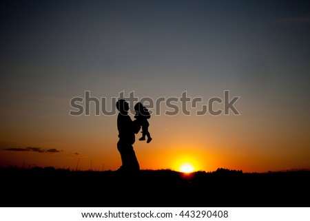 Silhouette of father and child on the outdoor on beautiful summer sunset - family