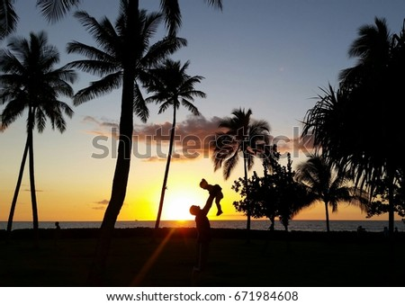 silhouette of father and daughter playing near beach