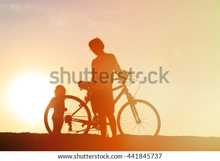 Silhouette of father and little daughter biking at sunset