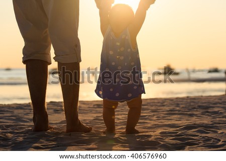 Silhouette of father and little daughter on beach