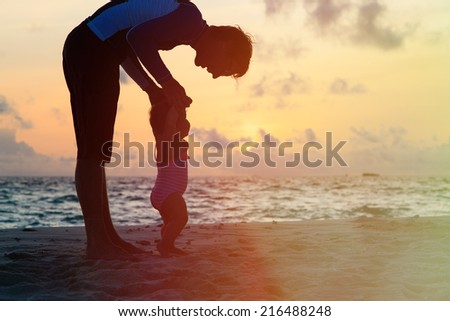 Silhouette of father and little daughter walking on sunset beach - stock photo