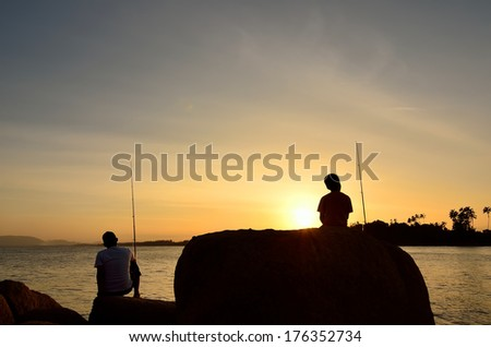 Silhouette of Father and son fishing in ocean surf at sunset. - stock photo