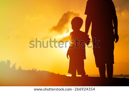 silhouette of father and son holding hands at sunset sea - stock photo