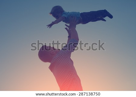 silhouette of father catching and playing with his son in the park in the evening (intentional sun glare and vintage color, lens focus on father) - stock photo