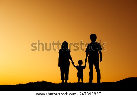 silhouette of  father mother and son playing outdoors at sunset