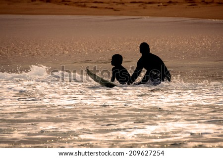 silhouette of father teaching son to surf - stock photo