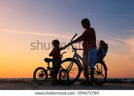 silhouette of father with two kids on bikes