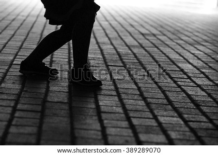 Silhouette of feet on the pavement