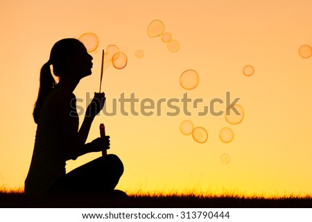 Silhouette of female blowing bubbles.  - stock photo
