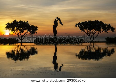 silhouette of female by the pool with sunset - stock photo